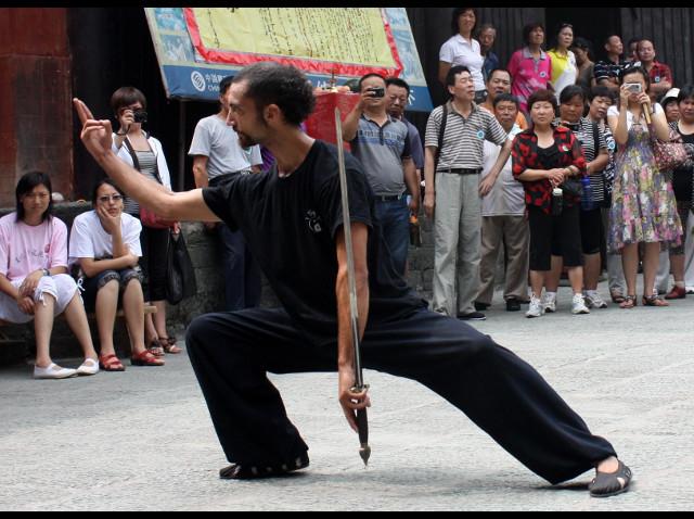 cercle de toursite chinois autour de Mathieu qui enchaine une forme traditionelle de Wudang à l'épée.