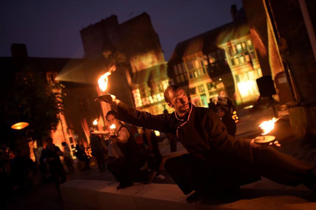 Gwenaëlle et Mathieu, de nuit, en postures basses sur un muret avec des mains de feu