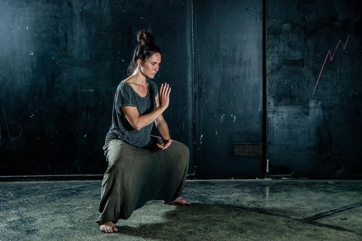 Qi gong. Gwenaëlle est en posture basse du cavalier, une main devant le cœur et l'autre devant le tan tien