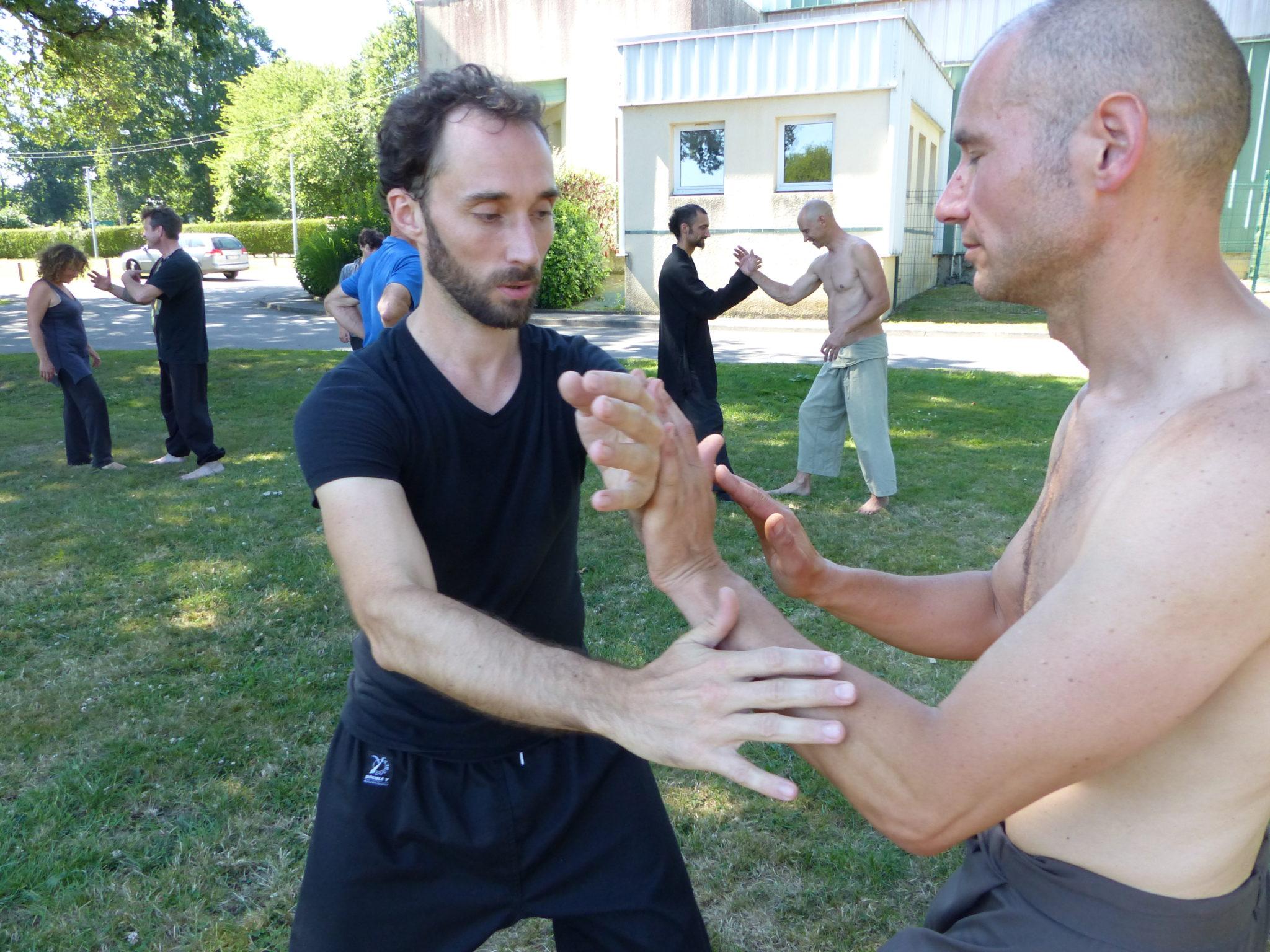 les pratiquants s'exerce à la poussé des mains, exercice classique du tai-chi