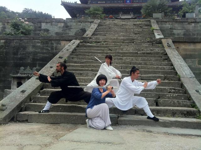 quatre pratiquants de kung-fu devant un temple chinois